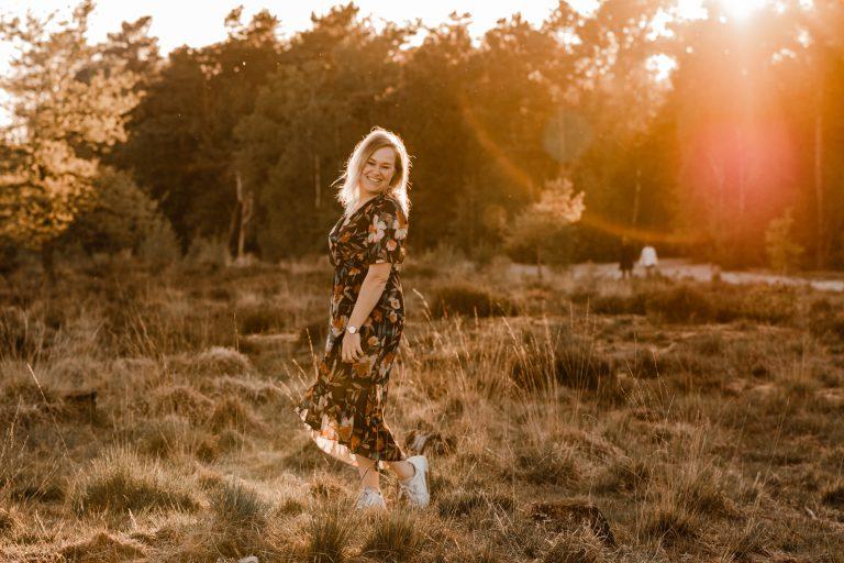puur susan fotograaf limburg sevenum met bloemetjesjurk, lensflare en danst in het gras