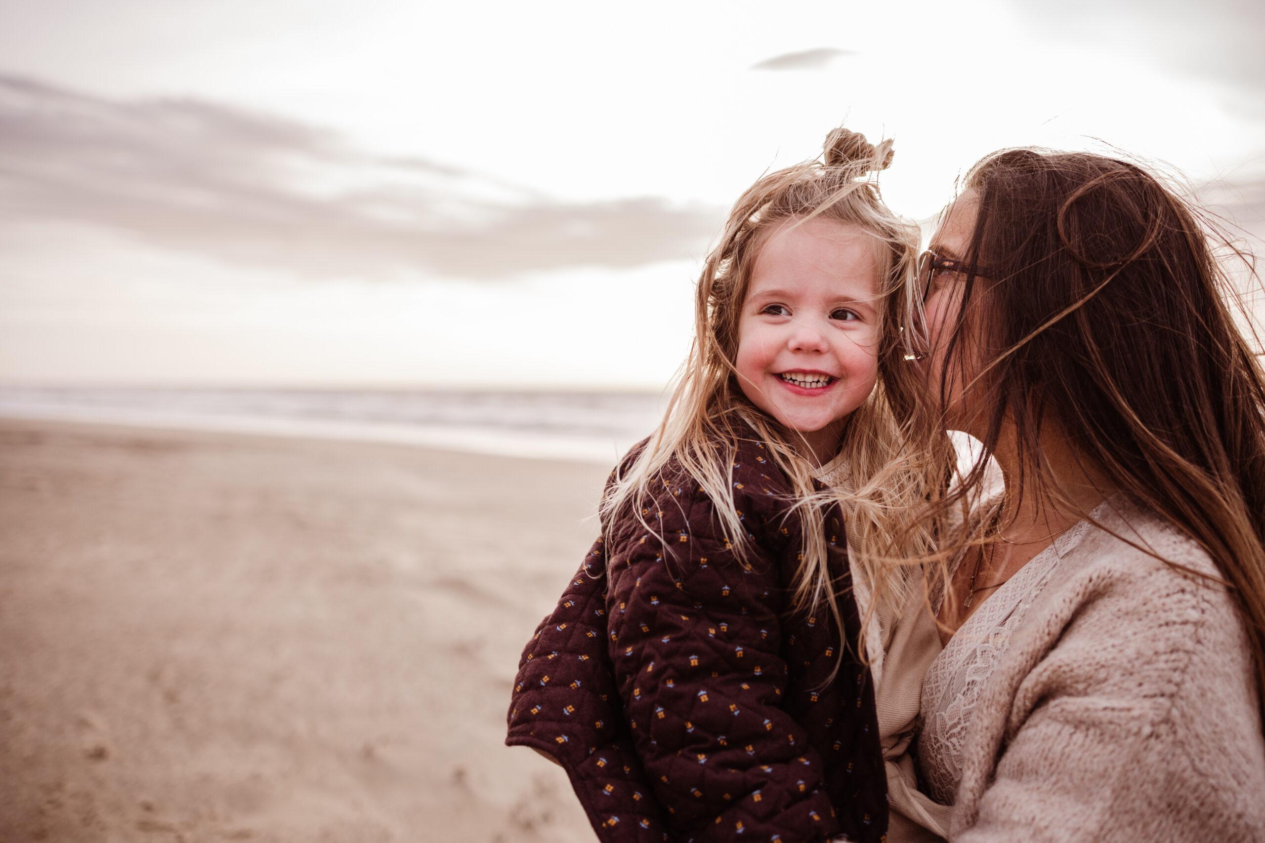 mamashoot motherhood kindershoot strand katwijk mama fluistert bij meisje in het oor
